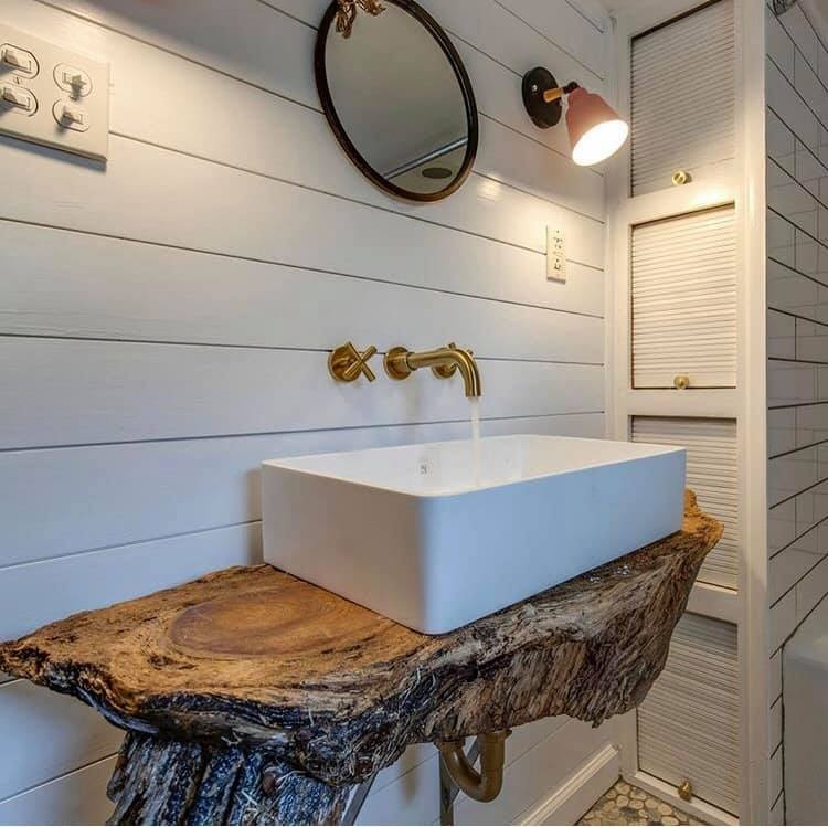 Rustic bathroom remodel with white sink and gold faucet fixtures. White wooded backsplash and woodsy tree trunk counter