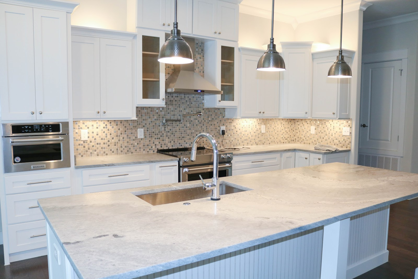 Beautiful kitchen with a large island and white cabinets and a light backwash.