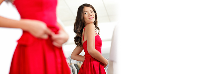 A woman with long, brown hair looking into a mirror while wearing a red dress.